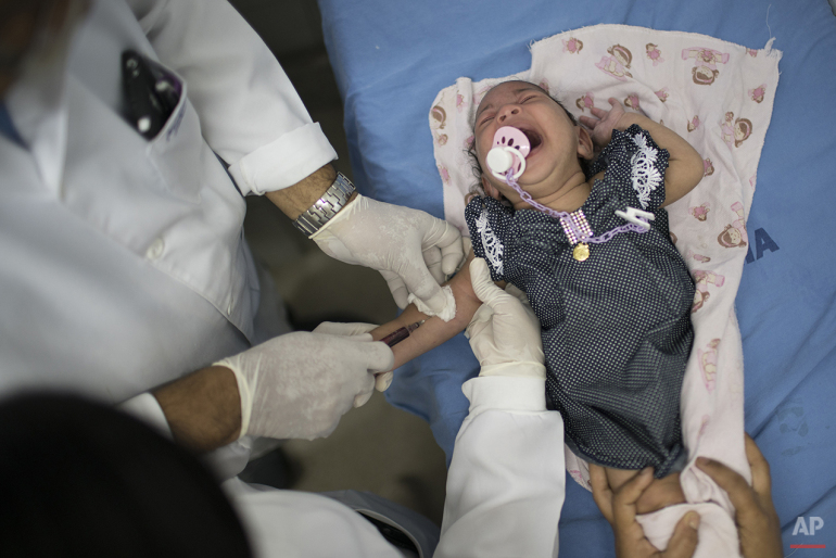 A doctor draw blood from Luana, who was born with microcephaly, at the Oswaldo Cruz Hospital in Recife, Brazil, Thursday, Jan. 28, 2016. Brazilian officials still say they believe there's a sharp increase in cases of microcephaly and strongly suspect the Zika virus, which first appeared in the country last year, is to blame. The concern is strong enough that the U.S. Centers for Disease Control and Prevention this month warned pregnant women to reconsider visits to areas where Zika is present. (AP Photo/Felipe Dana)